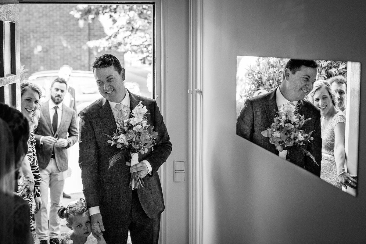 first_look bruidspaar voordeur ophaalmoment zart-wit foto documentair bruidsfotograaf breda natuurlijke documentaire trouwfotografie houtse_meer journalistieke bruidsfotografie