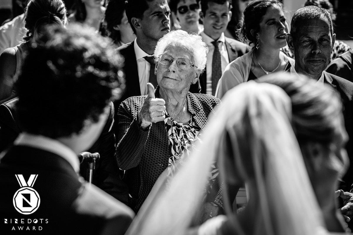 oma bruidspaar geeft duim omhoog thumbs_up trouwceremonie buiten trouwen landgoed_wolfslaar breda ongedwongen zwart_wit journalistieke bruidsfoto reportage trouwfoto documentaire trouwfotografie bruidsfotografie