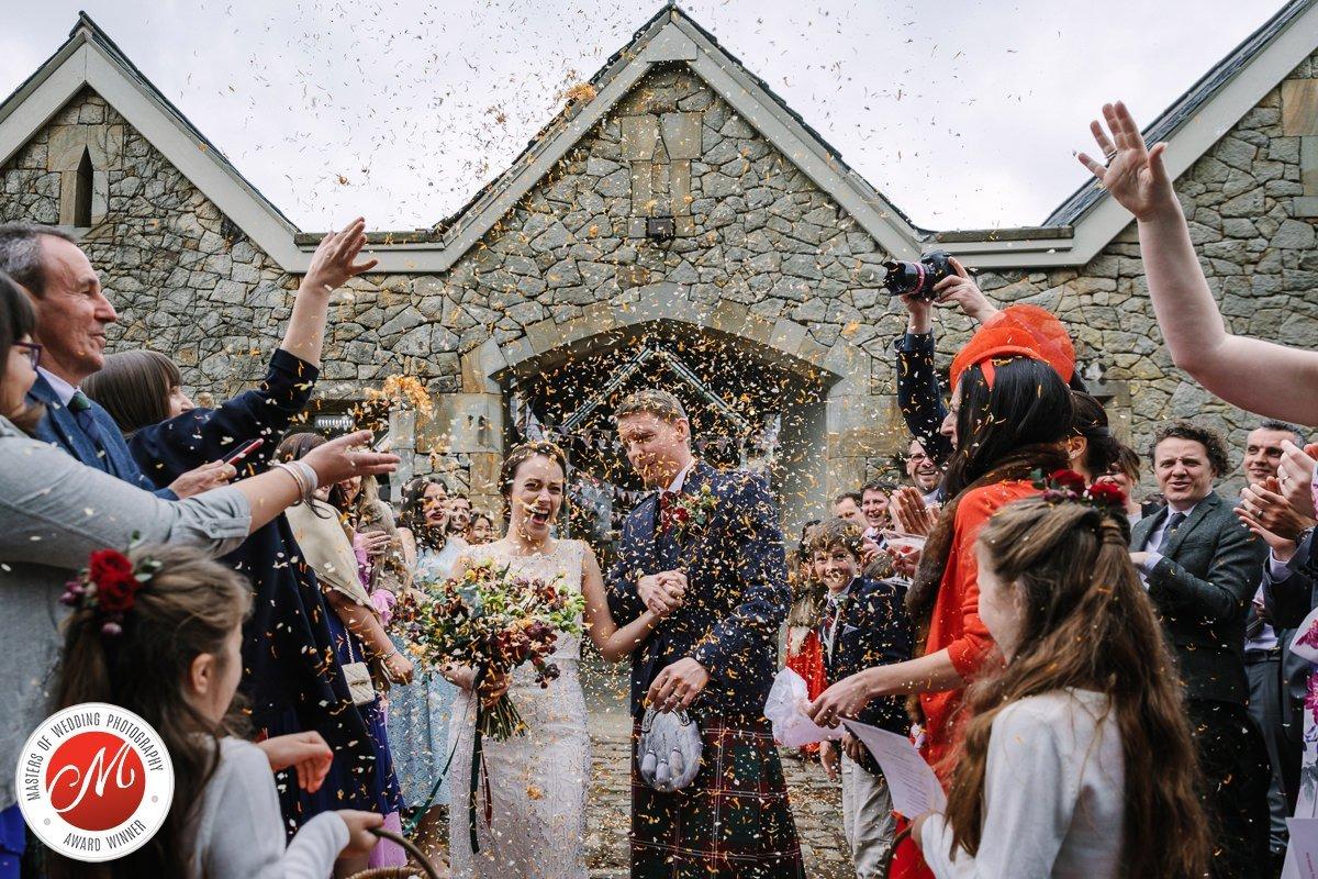 engels bruidspaar confetti regen bruidsgasten bruidegom schotse kilt award-winning ongedwongen journalistieke bruidsfoto reportage trouwfoto documentaire trouwfotografie bruidsfotografie destination_wedding engeland
