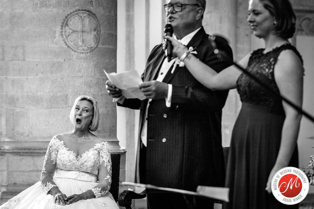 bruid kijkt verrast tijdens trouwceremonie grote_kerk breda ongeposeerde zwart-wit trouwfoto journalistieke bruidsfoto reportage trouwfoto documentaire trouwfotografie bruidsfotografie