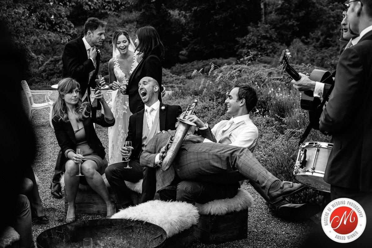 bruidsgasten bruiloft buiten muziek saxofoon plezier lachen zwart-wit trouwfoto journalistieke bruidsfoto reportage trouwfoto documentaire trouwfotografie bruidsfotografie