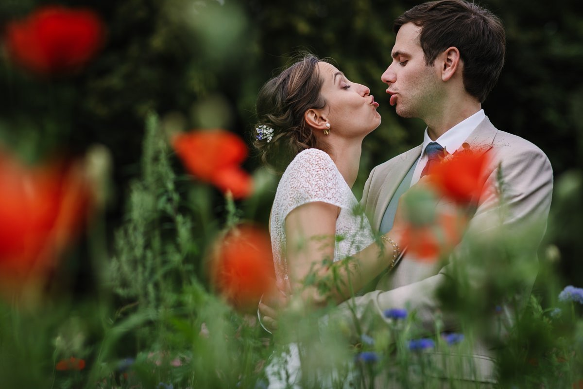 ongeposeerde trouwfoto bruid bruidegom kussen buiten bloemenveld rode klaprozen journalistieke bruidsfoto reportage trouwfoto documentaire trouwfotografie bruidsfotografie