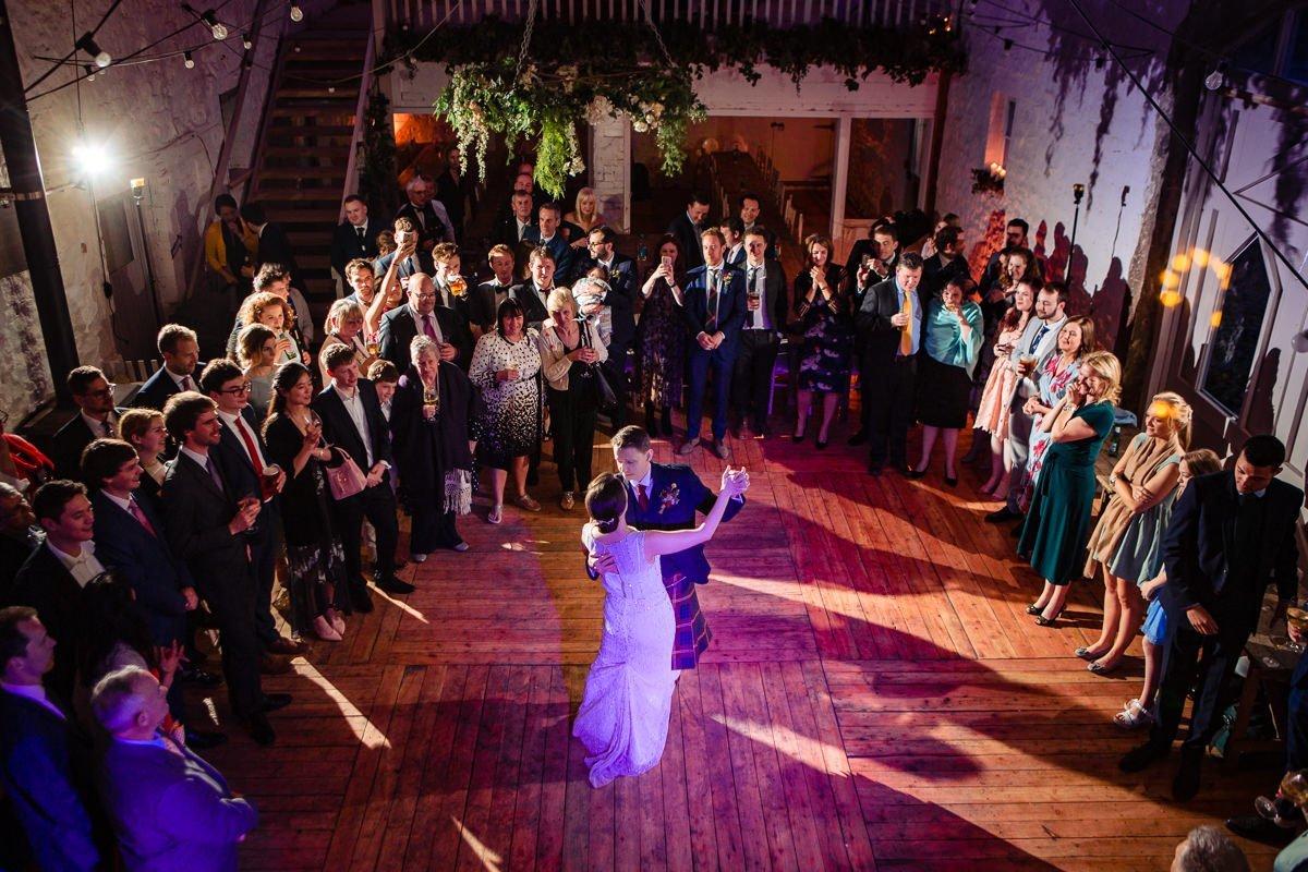 bruid bruidegom openingsdans bruiloftsgasten off_camera_flash ocf journalistieke bruidsfoto reportage trouwfoto hoog perspectief van bovenaf documentaire trouwfotografie bruidsfotografie