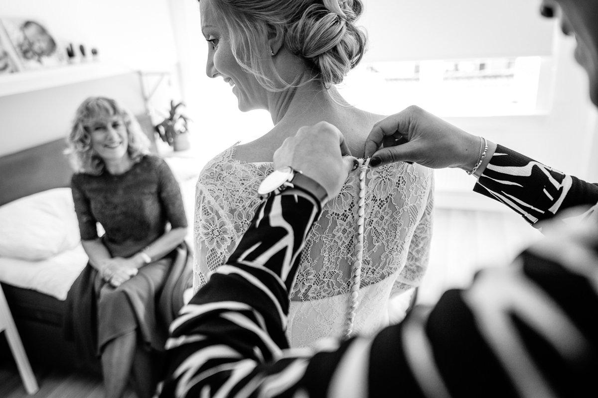 bruid voorbereidingen aankleden bruidsjurk knoopjes zwart_wit journalistieke bruidsfoto reportage trouwfoto documentaire trouwfotografie bruidsfotografie