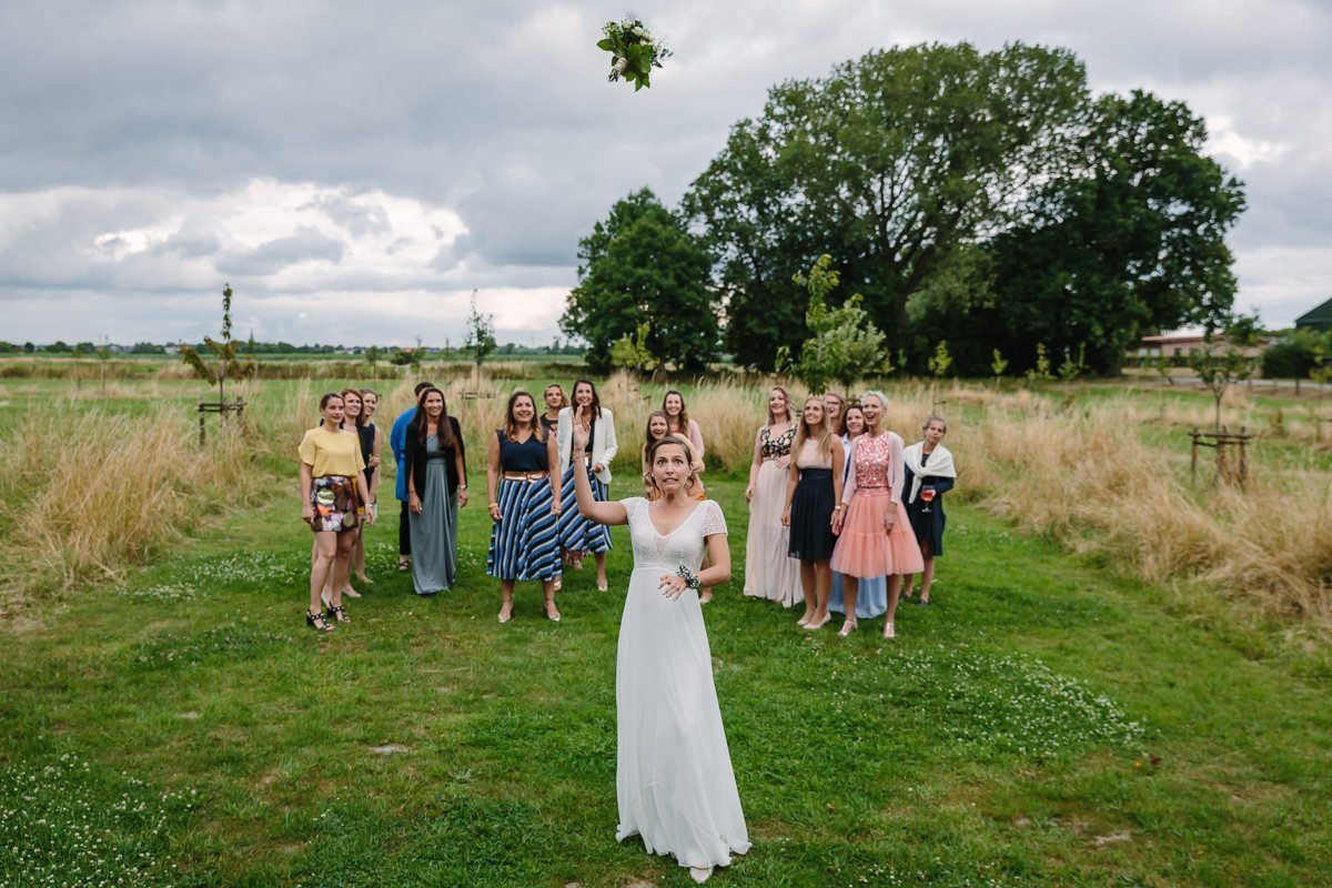 bruid bruidsboeket gooien bloemen bruidsgasten journalistieke bruidsfoto reportage trouwfoto documentaire trouwfotografie bruidsfotografie