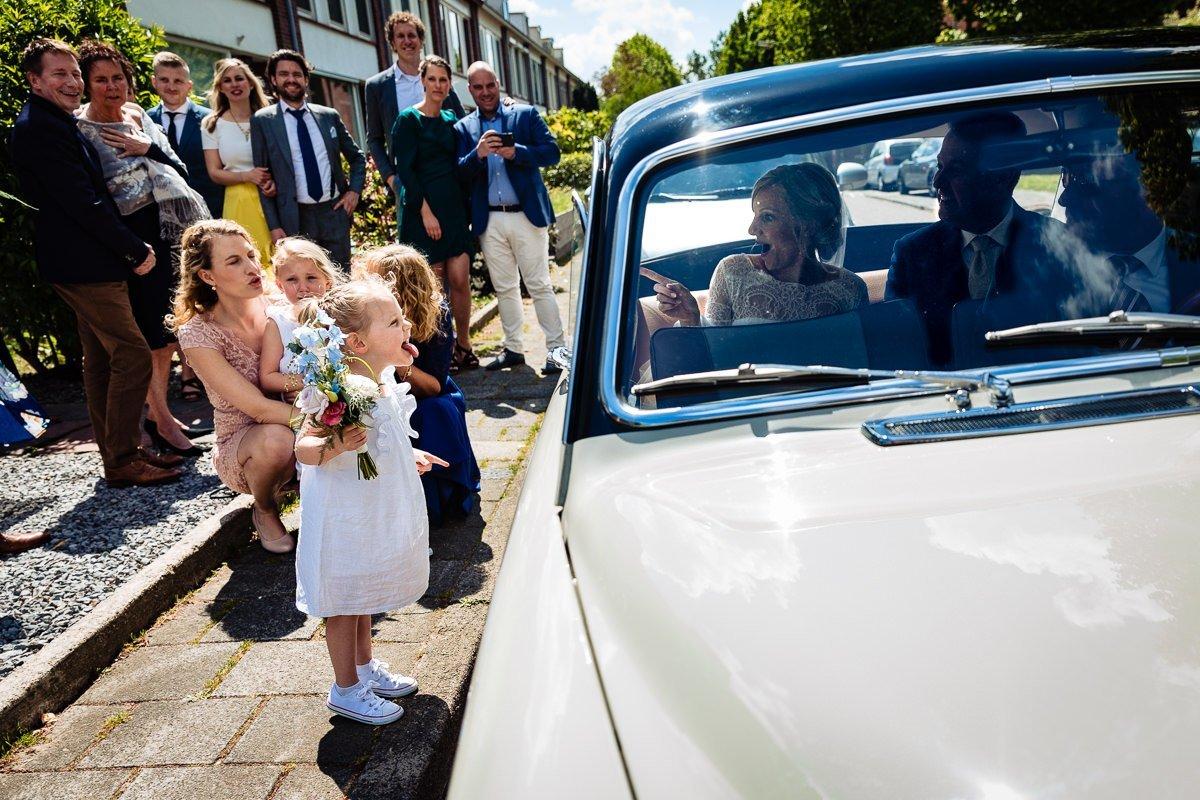 ongeposeerde trouwfoto bruid bruidegom bruidsauto bruidsmeisjes steken tong uit journalistieke bruidsfoto reportage trouwfoto documentaire trouwfotografie bruidsfotografie breda