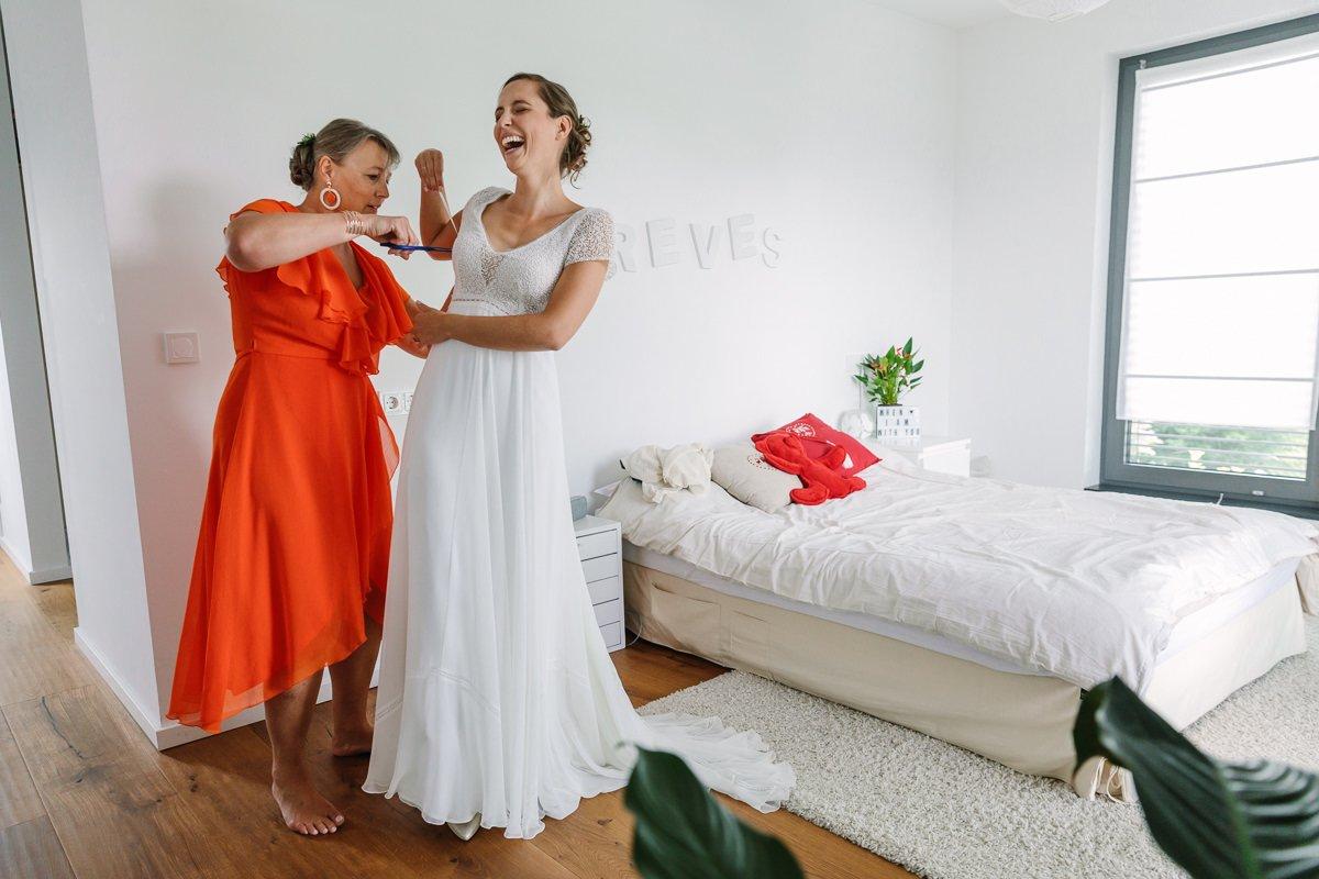 bruid voorbereidingen aankleden bruidsjurk trouwjurk moeder oranje jurk schaar lusje journalistieke bruidsfoto reportage trouwfoto documentaire trouwfotografie bruidsfotografie