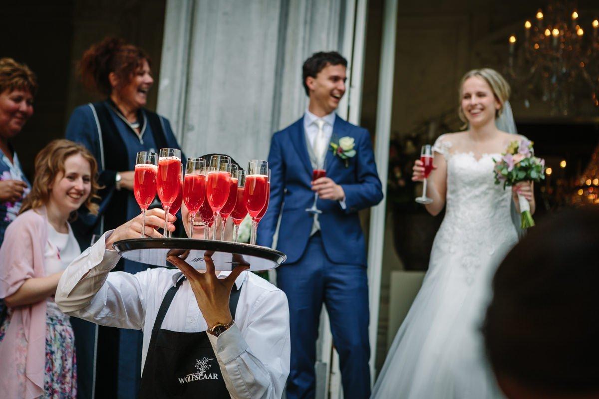 bruid bruidegom toast focus op rode champagne glazen landgoed_wolfslaar journalistieke bruidsfoto reportage trouwfoto documentaire trouwfotografie bruidsfotografie