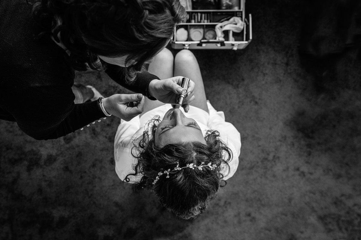bruid voorbereidingen make_up trouwdag zwart_wit trouwfoto bruidsfoto hoog perspectief bovenaf journalistieke bruidsfoto reportage trouwfoto documentaire trouwfotografie bruidsfotografie