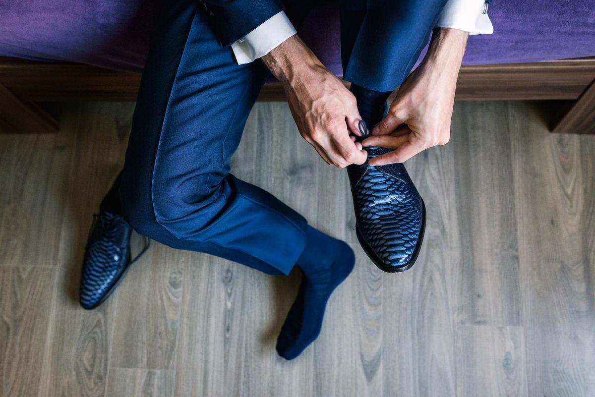 bruidegom voorbereidingen aankleden bruidsschoenen journalistieke bruidsfoto reportage trouwfoto hoog perspectief bovenaf documentaire trouwfotografie bruidsfotografie