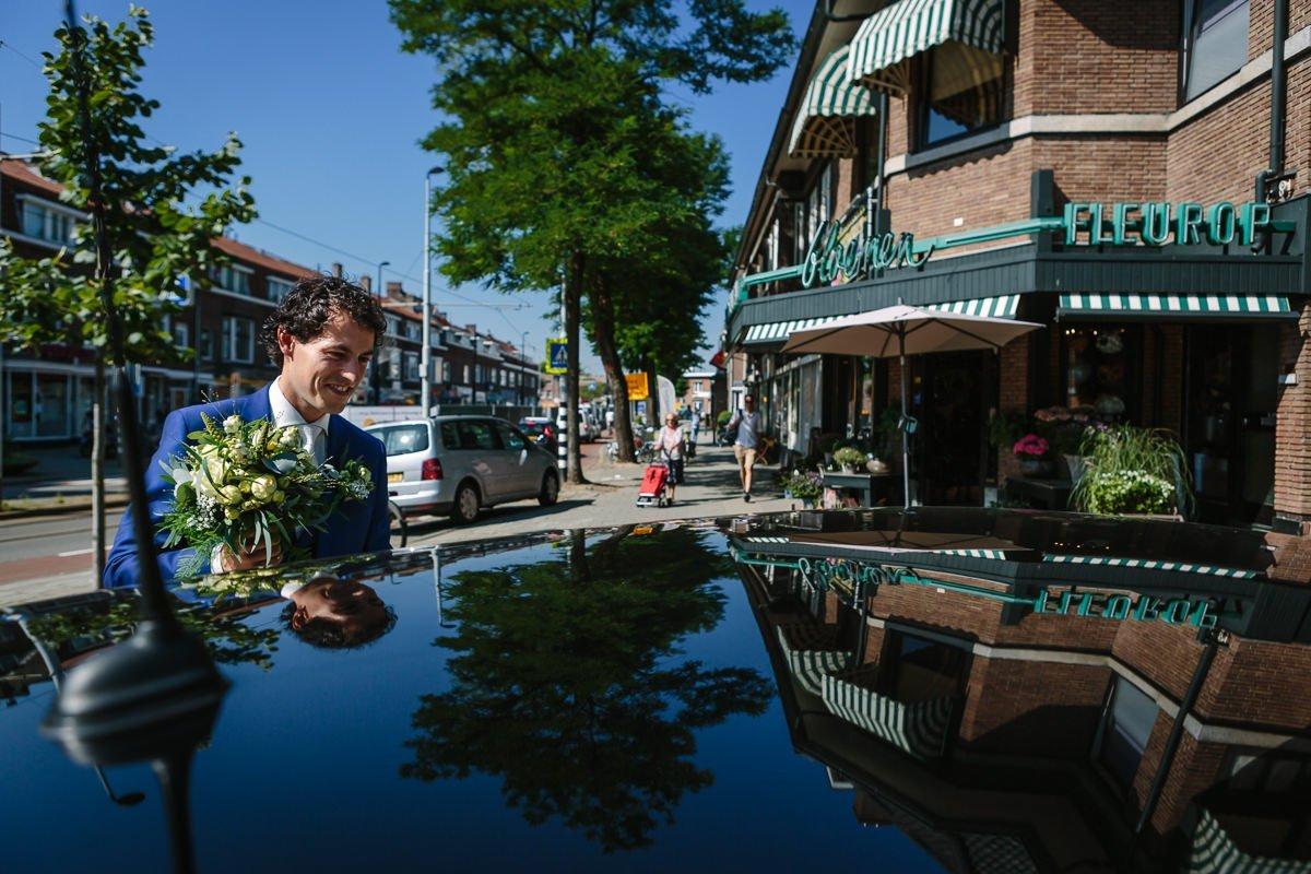 bruidegom voorbereidingen ophalen bruidsboeket reflectie dak bruidsauto journalistieke bruidsfoto reportage trouwfoto hoog perspectief bovenaf documentaire trouwfotografie bruidsfotografie