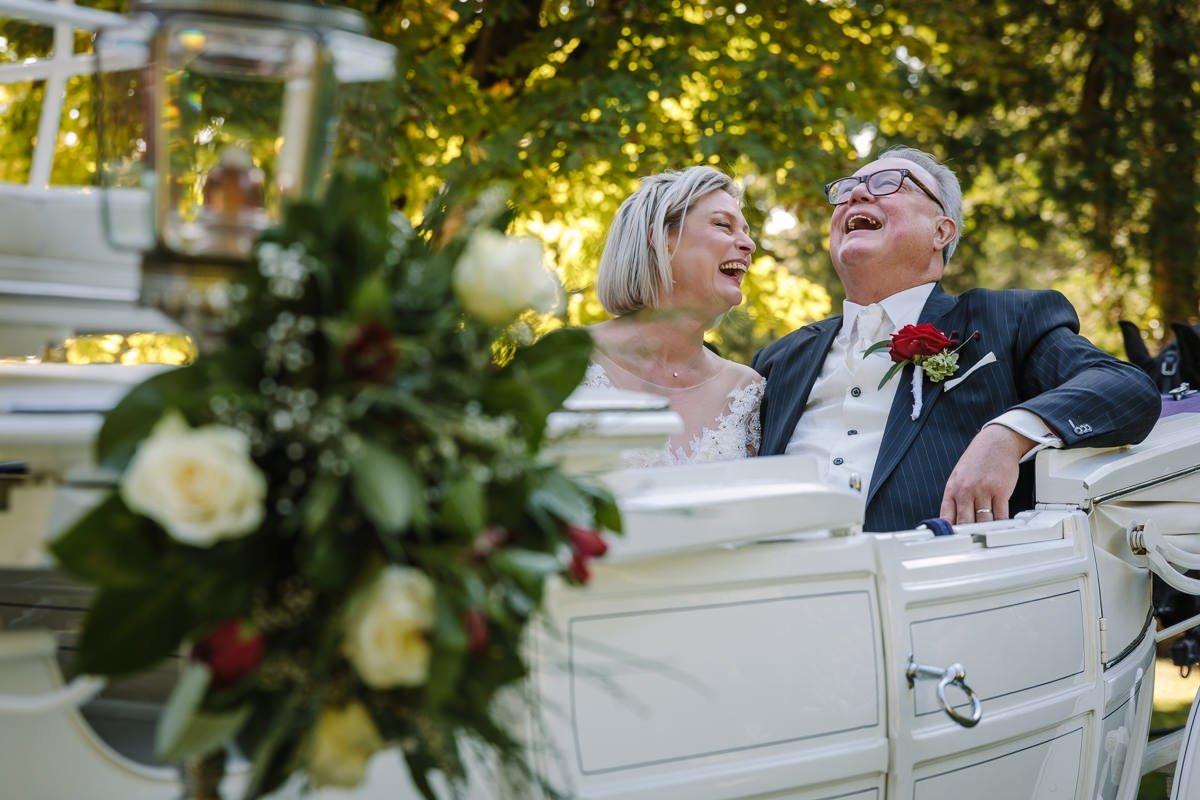 bruid bruidegom plezier trouwfoto bruidsfoto buiten lachend trouwkoets paarden landgoed_wolfslaar journalistieke bruidsfoto reportage trouwfoto documentaire trouwfotografie bruidsfotografie