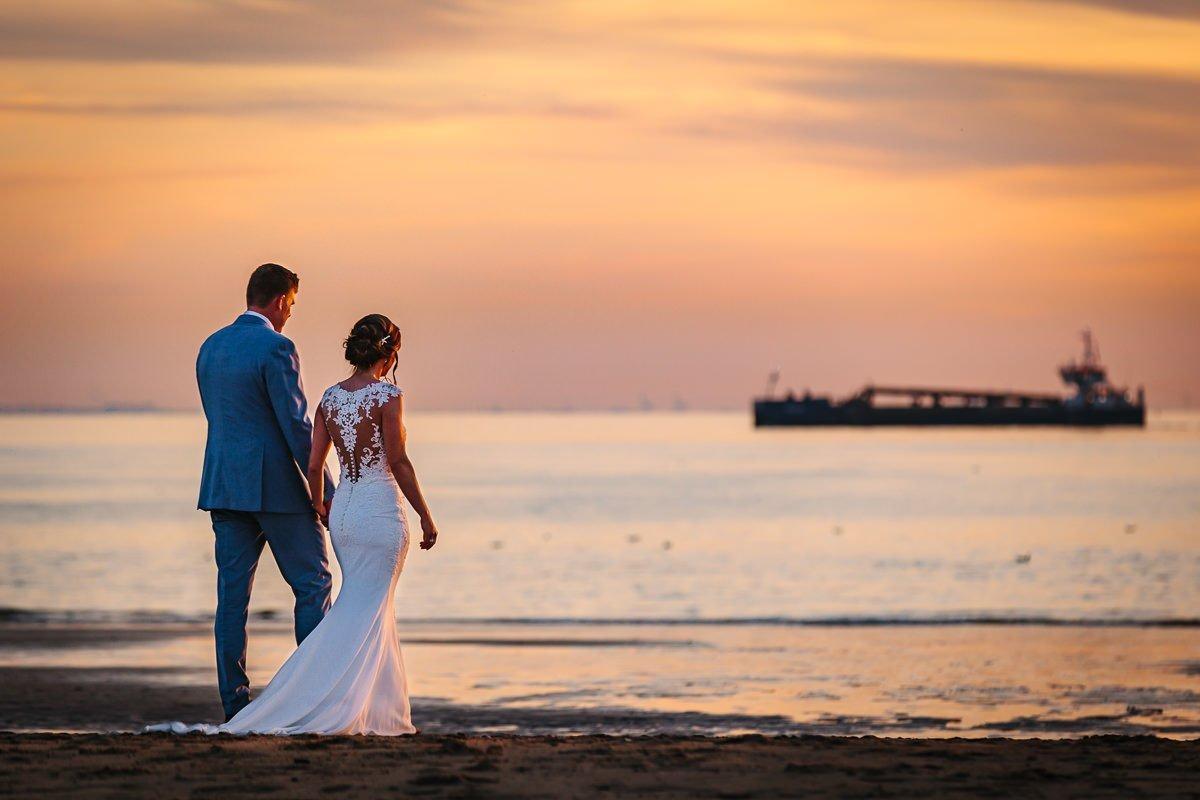 bruid bruidegom lopen hand_in_hand strand zonsondergang golden_hour kaapduin zeeland journalistieke bruidsfoto reportage trouwfoto documentaire trouwfotografie bruidsfotografie