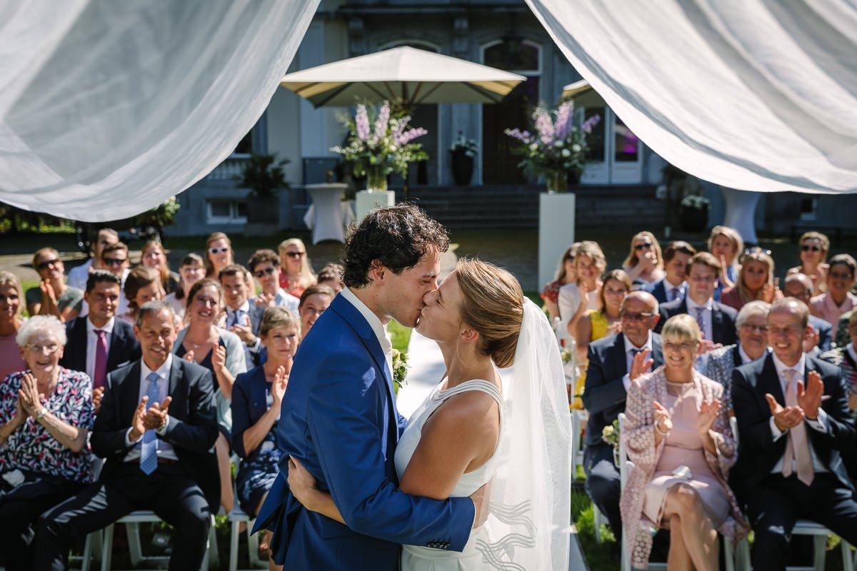 bruid bruidegom trouwceremonie buiten landgoed_wolfslaar breda kus bruidsfoto trouwfoto journalistieke bruidsfoto reportage trouwfoto documentaire trouwfotografie bruidsfotografie