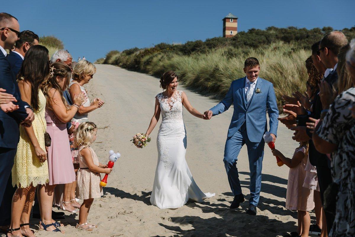 bruid bruidegom aankomst trouwceremonie buiten strand zeeland kaapduin bruidsfoto trouwfoto journalistieke bruidsfoto reportage trouwfoto documentaire trouwfotografie bruidsfotografie