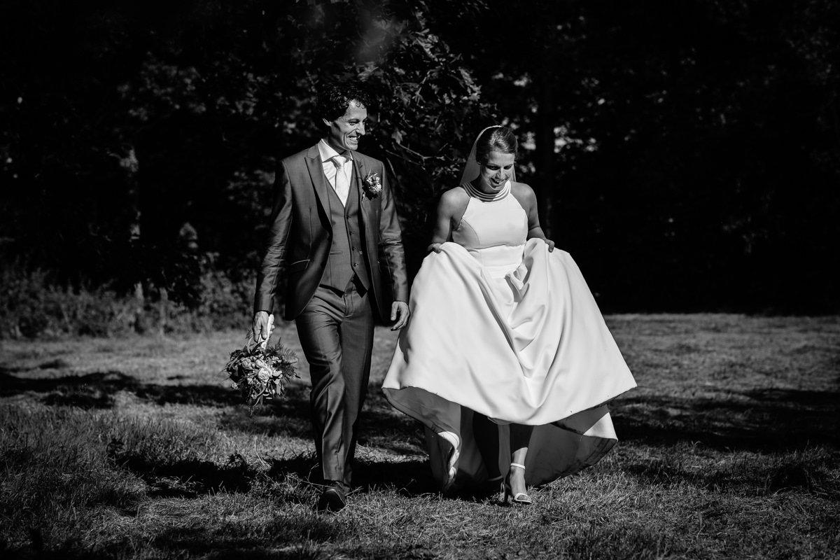 bruid bruidegom lopen buiten landgoed_wolfslaar zwart_wit journalistieke bruidsfoto reportage trouwfoto documentaire trouwfotografie bruidsfotografie