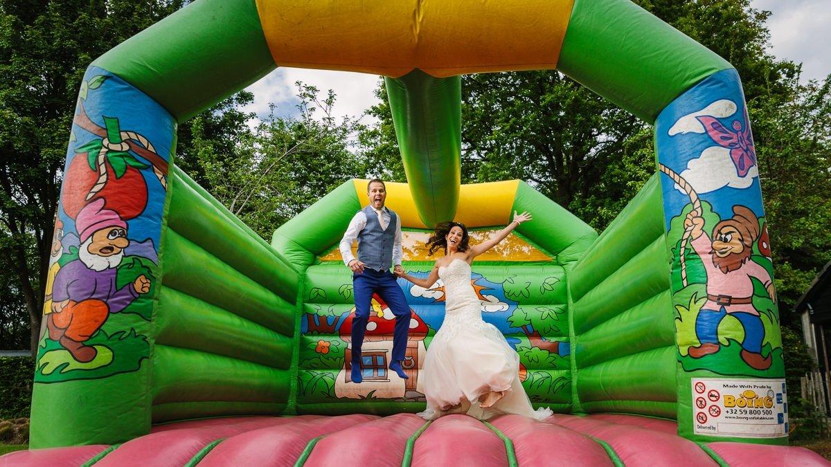bruid bruidegom bruidspaar springen springkussen groen roze breda journalistieke bruidsfoto reportage trouwfoto documentaire trouwfotografie bruidsfotografie