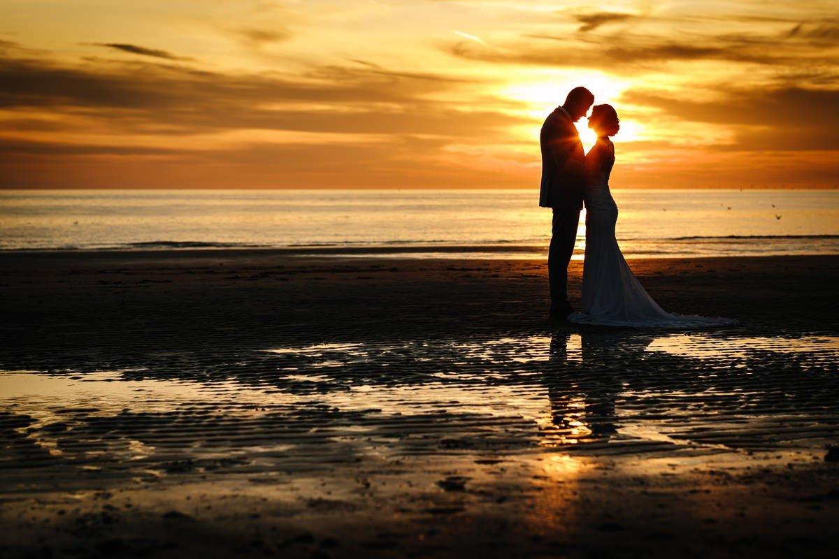 bruid bruidegom trouwfoto bruidsfoto zonsondergang strand silhouette bruidspaar journalistieke bruidsfoto reportage trouwfoto documentaire trouwfotografie bruidsfotografie