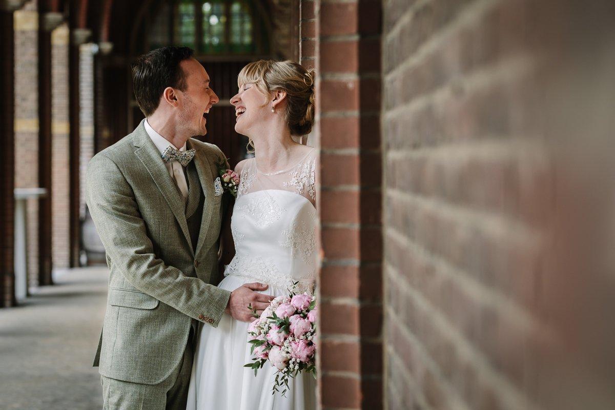 bruidspaar bruidsfoto bovendonk hoeven bruid bruidegom trouwfoto leunen muur galerij lachen blij documentaire natuurlijke authentieke journalistieke bruidsfotografie trouwfotograaf breda brabant