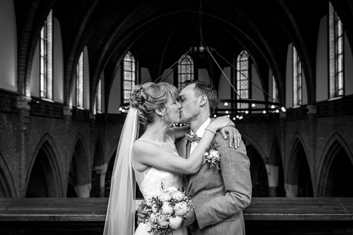 bruidspaar bruidsfoto zwart-wit bovendonk hoeven bruid bruidegom trouwfoto kus zoen kapel binnen documentaire natuurlijke authentieke journalistieke bruidsfotografie trouwfotograaf breda brabant